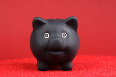 Black piggy bank standing on red sand in front of red background Stock Images