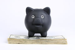 Black piggy bank standing on stack of money american hundred dollar bills on white background. Black piggy bank standing on stack of money american hundred Stock Photos