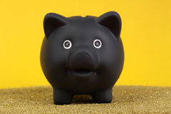 Black piggy bank standing on yellow, gold sand in front of yellow background Royalty Free Stock Image