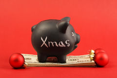 Black piggy bank with text Xmas standing on stack of money american hundred dollar bills and three red matt christmas balls Royalty Free Stock Photos