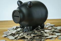 Black piggy bank on top of coins as saving or financial wealth c stock images