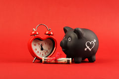 Black piggy bank with white heart and heart alarm clock and gift of money american hundred dollar bills with red ribb Royalty Free Stock Photo