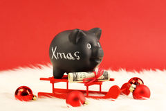 Black piggy bank with white text Xmas and gift of money with red ribbon on money american hundred dollar bills on red sled Royalty Free Stock Images