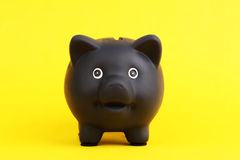 Black piggy bank on yellow background Stock Photo