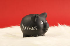 Black piggy box with text Xmas standing on white fur on red background Stock Image
