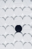 Black pill surrounded by white prescription pills on white background Royalty Free Stock Images