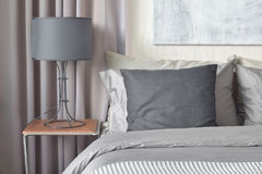 Black pillow on bed and black shade lamp on bedside table Stock Photography