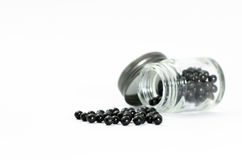 Black  pills Placed on a white background and in a glass bottle. Royalty Free Stock Photography