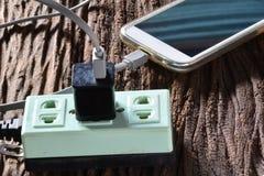 Black pin plug and green plug socket and charging smart phone on Stock Photos