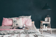 Black and pink bedroom in loft style. Black and pink stylish loft bedroom. Unmade bed with breakfast and reading on tray. Lamp and interior decor over blank Stock Image