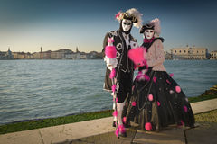 Black and pink costumed masked couple. At San Giorgio in Venice Royalty Free Stock Images
