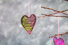 Black-pink hearts hang on branches on a gray concrete background. Love tree. The concept of Valentine's Day. A symbol of love. Black-pink hearts hang on stock photo