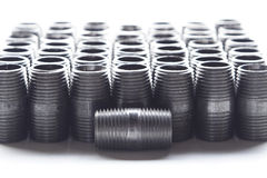 Black Pipe Fittings. Rows of black pipe nipples behind a single pipe nipple laying on it's side royalty free stock images