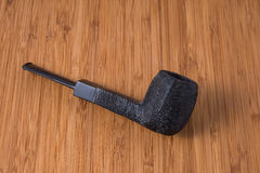 Black Pipe. A black pipe handcrafted on a wood table Stock Image