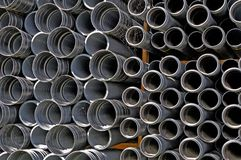 Black tubes stored at construction site. Black pipes for plumbing and sewage stacked up at construction site Stock Photo