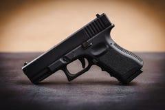 Black pistol on a black table. Black 9mm pistol on a black wooden table Stock Photos