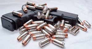 A black pistol with bullets on it and next to it. A black semi automatic pistol with .40 caliber hollow point bullets laying on the gun and next to it. Shot with Royalty Free Stock Photography
