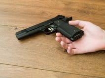 Black Pistol Gun in Dead Hand stock image