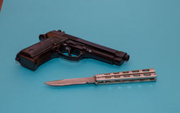 Black pistol and iron knife on a blue background Stock Photo