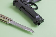 Black pistol and iron knife on a light green background Stock Image