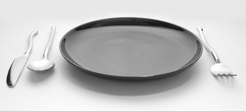 Black place setting with plate knife fork and spoon Royalty Free Stock Photo