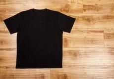 Black shortsleeve cotton tshirt on a wooden backgronud stock photos