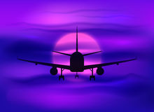 Black plane silhouette in dark purple sunset sky Stock Images