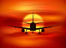 Black plane silhouette at red sunset background Royalty Free Stock Image