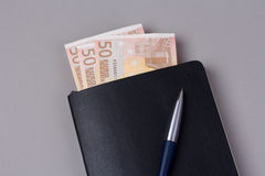 Black daily planner with luxury ball pen and some. Close up black daily planner with luxury ball pen and some euro banknotes on grey background Royalty Free Stock Photos
