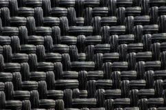Black plastic basketwork pattern process of weaving or sewing pliable materials. A Black plastic basketwork pattern process of weaving or sewing pliable stock photo