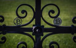 Black plastic Bit Coin on steel rusty old fence in a sun royalty free stock photo