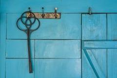 Black plastic carpet beater hangs on blue wall Stock Photos