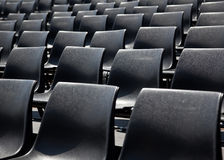 Black plastic chairs. Arranged in rows, outside Stock Photo