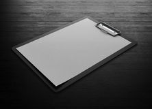 Black plastic clipboard with blank paper sheet. On a black wooden background. 3d rendering Stock Photos