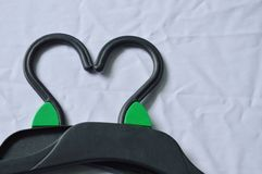 Black plastic clothes hanger arranging heart shape on white fabric background Royalty Free Stock Images