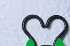 Black plastic clothes hanger arranging heart shape on white fabric background Royalty Free Stock Photos