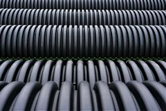 Black plastic curvilinear PVC pipe. Stacked tubes of corrugated polyethylene align in the distance.  Hollow and set for drainage during construction, the ridges Royalty Free Stock Photos