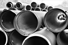 Black plastic curvilinear PVC pipe. Stacked tubes of corrugated polyethylene align in the distance.  Hollow and set for drainage during construction, the ridges Royalty Free Stock Images