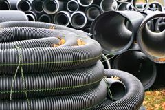Black plastic curvilinear PVC pipe. Stacked tubes of corrugated polyethylene align in the distance.  Hollow and set for drainage during construction, the ridges Stock Photography
