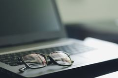 Black plastic eye glasses, placed on a portable computer On the desk, feeling lonely from work Concept of rest after hard work royalty free stock image