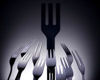 Black plastic fork surrounded by silver cutlery Stock Images