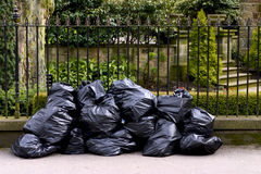 Black plastic garbage bags sidewalk / pavement Stock Image