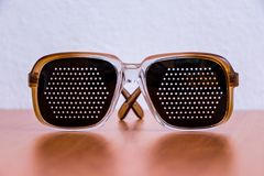 Black plastic glasses on a brown table. _ Stock Image