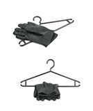 Black plastic hanger isolated. Black plastic hanger with a pair of leather gloves over it, composition isolated over the white background, set of two different Stock Photo