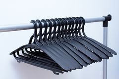 black plastic hangers hang on a light background. many different hangers stock image