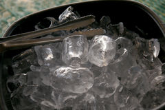 Black plastic ice bucket and stainless steel ice tongs. Royalty Free Stock Photos