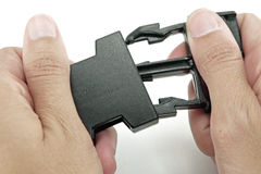 Black plastic lock buckle is locked by both hands on white backg. Round Royalty Free Stock Photography