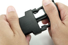 Black plastic lock buckle is locked by both hands on white backg. Round Stock Photos
