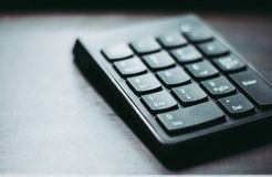 A black plastic numeral keypad is placed on the wooden table. Focused on the bottom half side with lighting source from left side Stock Image