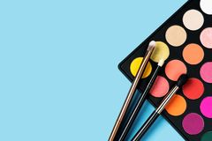 Black plastic palette of brightly coloured eyeshadow and three make-up brushes laying on top of the palette arranged in the corner. Of pastel baby blue stock images